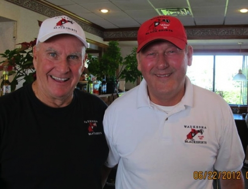Dan Steffan'61; Alan Garrett '60 model the Blackshirt t shirt, golf shirt and hats available for purchase.